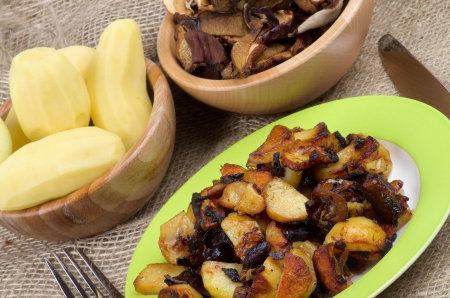 prepared potato: Roasted Potato with Mushrooms, Onion and Spices  Arrangement of Prepared Potato on Green Plate and Two Wood Bowls with Raw Potato and Slices of Mushrooms and Fork with Knife close up
