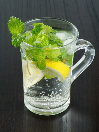 Glass Cup of Beverage with Mint Leafs, Lemon and Ice Cubes closeup on Black Wood background  photo