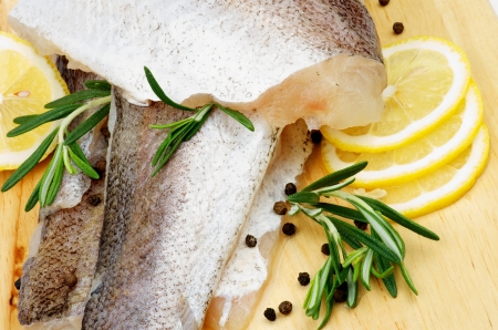 Arrangement of Fillet Raw Fish Hake, Lemon and Rosemary with Black Peppercorn closeup on Cutting Board Stock Photo