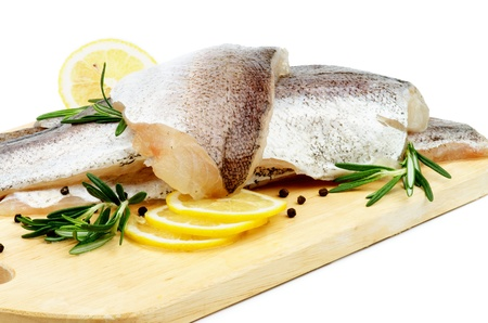 Raw Fish Hake Fillets with Lemon, Black Peppercorn and Rosemary on Cutting Board closeup on white background Foto de archivo