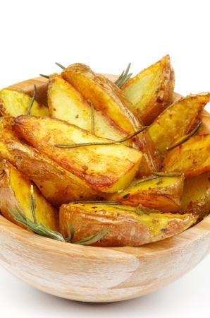 Gebratene Potato Wedges mit Rosmarin und Kräuter in Holzschale Nahaufnahme auf weißem Hintergrund