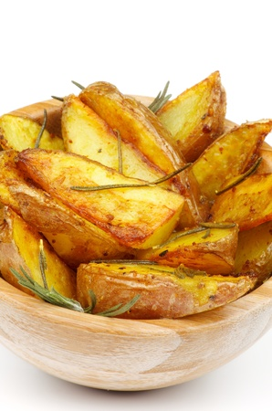Roasted Potato Wedges with Rosemary and Herbs in Wooden Bowl closeup on white background photo