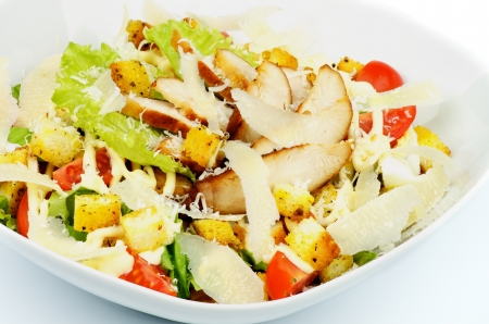 Caesar Salad with Garlic Crouton, Romaine Lettuce, Cherry Tomato, Eggs, Sauce and Grated Parmesan Cheese and Arrangement of Grilled Chicken Breast closeup in White Bowl photo