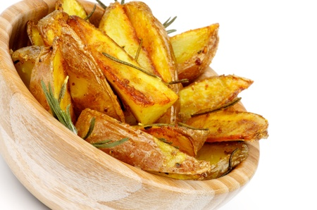 Wooden Bowl with Roasted in Rosemary Potato Wedges closeup on white background