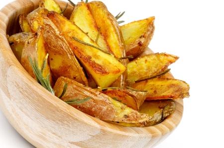Tazón de fuente de madera con asado de patatas romero Wedges primer en el fondo blanco Foto de archivo