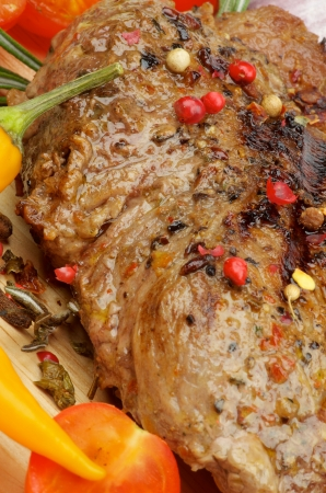 Roasted Beef with Spices, Peppercorns and Herbs closeup on Wooden Board with Vegetables
