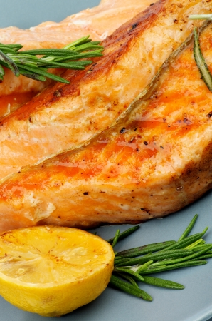 Delicious Grilled Salmon with Lemon and Rosemary closeup on Green Plate photo