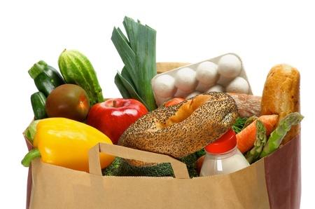 Bolsa de Productos alimenticios con verduras, pan, verduras, frutas, una botella de leche y contenedores de huevos aislados sobre fondo blanco