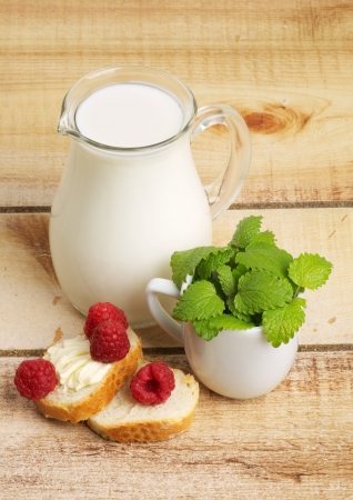 Healthy Breakfast with Jug of Milk, Raspberries, Mint Leafs and Toasts on Wooden background. Stock Photo