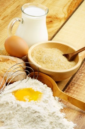 Preparing Dough  Ingredients with Jar of Milk, Flour, Egg, Sugar and Wooden Spoon with Egg Whisk closeup on Wooden background photo