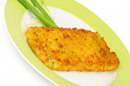 Breaded Сod Fillet Garnished with Spring Onion on Green Plate closeup photo