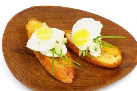 Delicious Snacks with Quail Egg, Cream Cheese, Cucumber, Spring Onion and Toasted Bread on Wooden Plate closeup photo