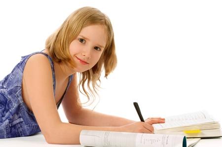 girl lying down: Chica rubia se acuesta y que estudia con los libros, Cuaderno de ejercicios y l�piz sobre fondo blanco Foto de archivo