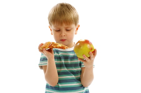 playful behaviour: Little Boy in Striped T-Shirt Making Hard Choice between Pizza and Apple  Stock Photo