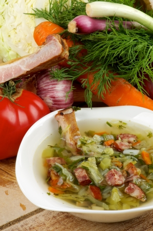 Gourmet Vegetable Soup with Smoked Pork Ribs in White Bowl and Ingredients with Cabbage, Tomatoes, Spring Onion, Leek, Carrot, Garlic and Greens on Wooden background
