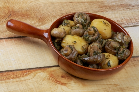 Delicious Stew with Champignon Mushrooms, Roasted Potato, Greens and Onion in Brown Frying Pan closeup on Wood background photo