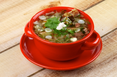 Delicious Vegetable Soup with Smoked Pork Ribs, Cabbage, Leek, Carrot, Garlic Greens and Sour Cream in Red Bowl isolated on Wooden background photo
