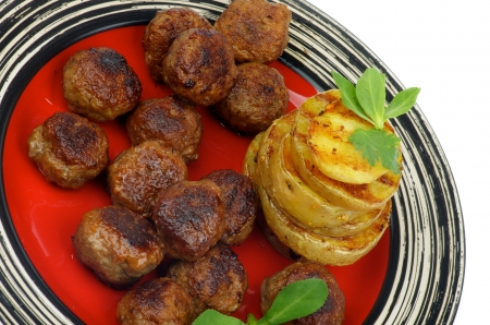 grilled potato: Delicious Roasted Meatballs and Stack of Grilled Potato with Greens closeup on Red Striped Plate