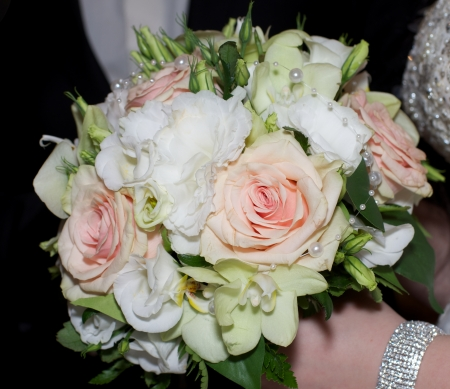 Beautiful Bridal Bouquet with Flowers and Pearls in Bride Hands photo