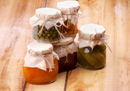 Arrangement of Jars with Homemade Preserves with Capers, Pickle Cucumbers, Strawberry and Apricot Jam, Pea and Carrot Mix on Wooden background photo