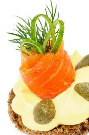 Delicious Snack with Smoked Salmon, Cheese Cream, Greens, Capers, Cucumber and Whole Grain Bread closeup on white  photo