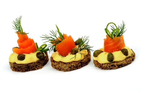 Delicious Snacks with Smoked Salmon, Greens, Cheese Cream and Capers In a Row isolated on white background  Horizontal View Foto de archivo