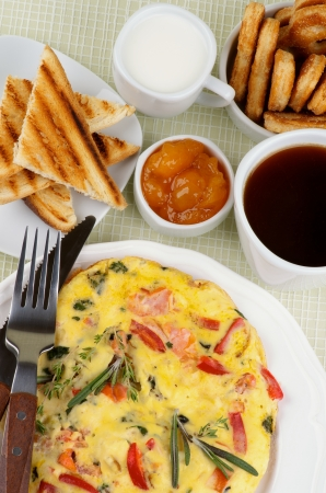 Hearty Breakfast with Delicious Omelet, Toasts, Apricot Jam, Cup of Coffee, Milk and Puff Pastry on light green Checkered background  Top View photo