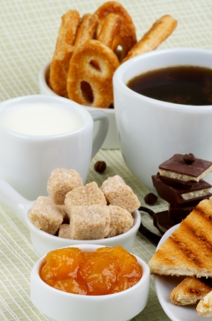 Arrangement of Coffee Cup, Milk, Puff Pastry, Apricot Jam and Toasts with Chocolate and Brown Sugar Cubes closeup on light green Checkered background photo
