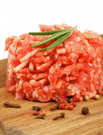 raw beef: Fresh Raw Beef Burger with Rosemary and Pepper Corns on Wooden Cutting Board isolated on white background