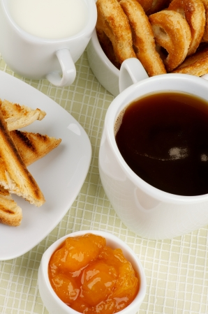 Coffee Break with Milk, Toasts, Apricot Jam and Puff Pastry closeup on Checkered background photo