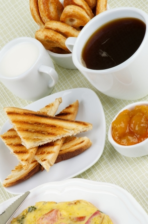 Delicious Hearty Breakfast with Toasts, Apricot Jam, Coffee, Milk and Puff Pastry closeup on light green Checkered background