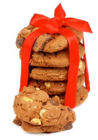 Stack of Delicious Christmas Cookies with Chocolate Pieces and Nuts Tied with Red Ribbon isolated on white background photo
