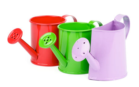 Purple, Green and Red Little Watering-Can In a Row isolated on white background photo