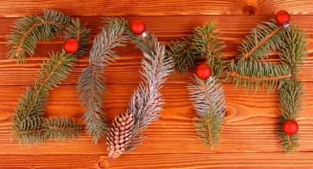 Arrangement of Spruce Branch, Fir Cone and Red Baubles as New Year 2014 closeup on Wooden background photo