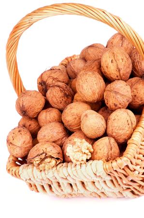 Wicker Basket with Ripe Walnuts closeup on white background photo