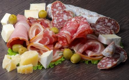 Disposición de Charcutería Embutidos de jamón, pepperoni, salami, Finocchiona, aceitunas verdes, Grana Padano y Camembert primer queso sobre fondo oscuro de madera Foto de archivo