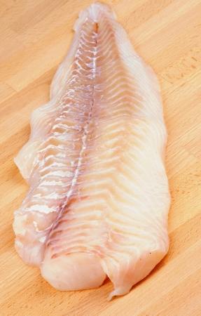 Raw Fresh Cod Fish Fillet closeup on Wooden Cutting Board