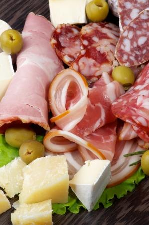 Heap von Delikatessen Aufschnitt mit geräuchertem Schinken, Peperoni, Salami, Finocchiona und verschiedene Käse mit Grana Padano, Camembert und Brie Nahaufnahme auf dunklem Holz Hintergrund Standard-Bild - 23121762