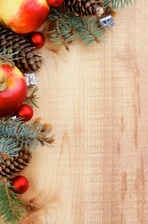 Corner Border of Spruce Branch, Red Baubles, Fir Cones and Delicious Apples closeup on Wooden background  Vertical View photo
