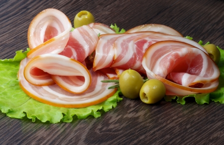 Anordnung der Scheiben Geräucherter Schinken mit grüne Oliven und Salat Nahaufnahme auf dunklem Holzuntergrund