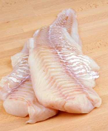 Two Slices of Raw Fresh Cod Fish Fillet closeup on Wooden Cutting Board Foto de archivo
