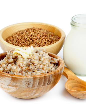 kasha: Arrangement of Traditional Russian Buckwheat Kasha with Buckwheat in Wooden Bowl, Milk and Wooden Spoon closeup on white background