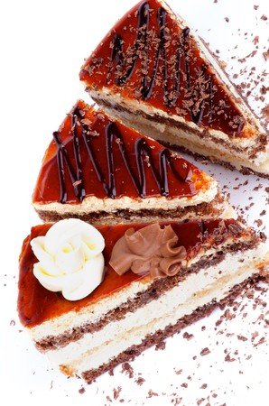 three layered: Three Slices of Delicious Cake with Glazed Cream and Grated Chocolate closeup on white background