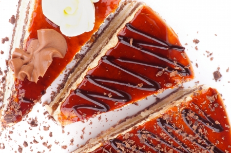 three layered: Three Slices of Delicious Cake with Glazed Cream and Grated Chocolate closeup on white background  Top View