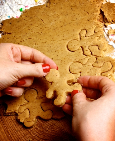 Hands of Women with Red Manicure Making Gingerbread Men with Dough and Flour on Wooden background photo