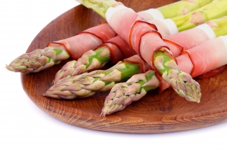 Asparagus Sprouts Wrapped in Smoked Bacon closeup on Wooden Plate photo