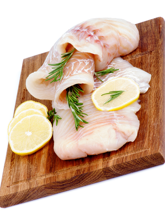Two Slices of Raw Cod Fish Fillet with Lemon and Rosemary on Wooden Cutting Board isolated on white background photo