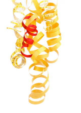 Arrangement of Yellow, Striped and One Red Hanging Curly Party Streamers isolated on white background photo