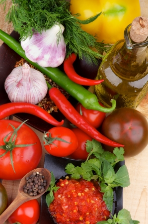 Arrangement of Bruschetta Sauce in Black Bowl with Tomatoes, Garlic, Chili Peppers, Dill, Peppercorn in Wooden Spoon and Olive Oil in Glass Bottle on Wooden background  Top View photo