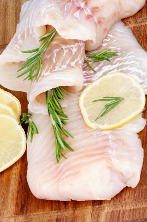 Raw Bacalao Filete de pescado con las rebanadas del limón y romero primer plano sobre fondo de madera Vista Vertical Foto de archivo